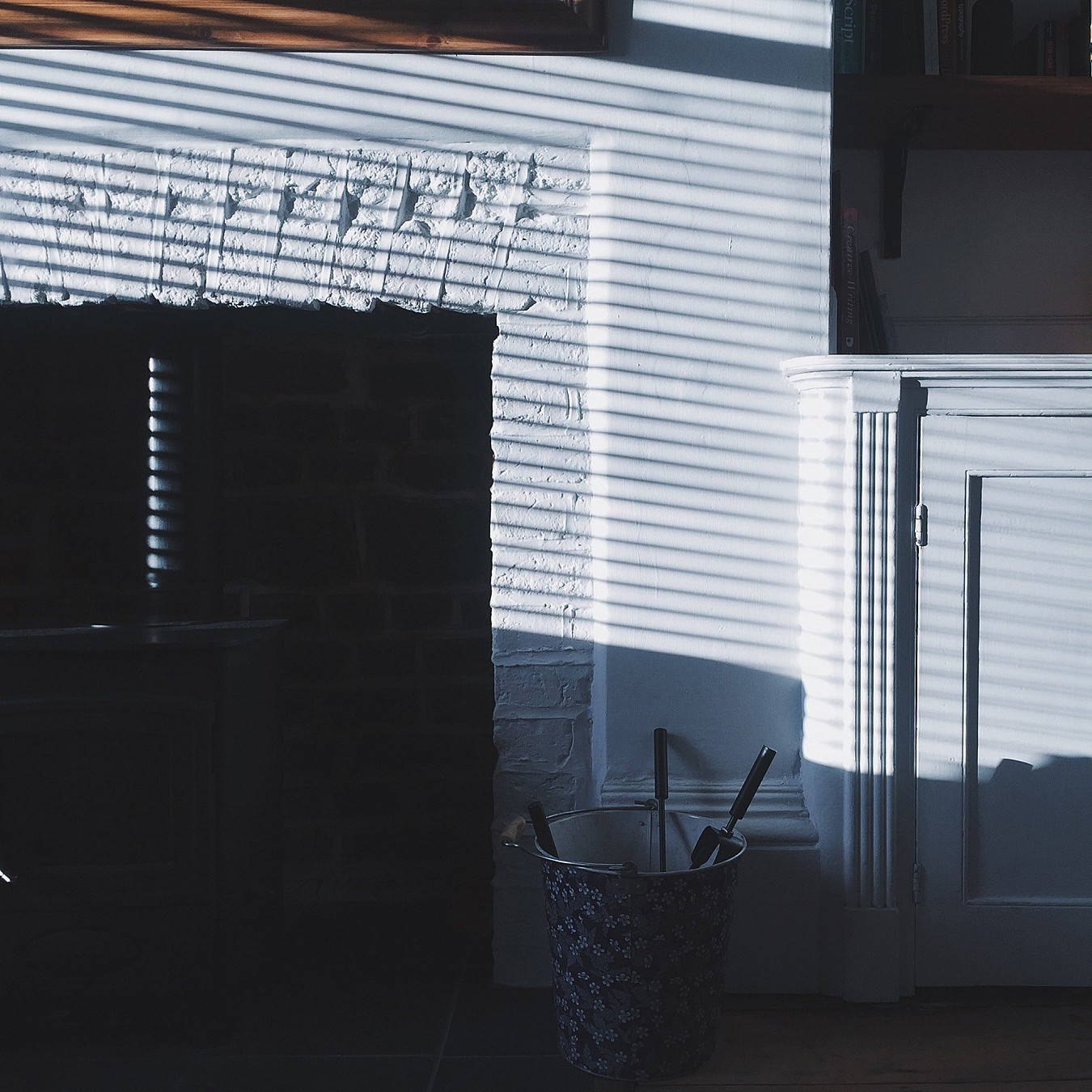 A fireplace with light streaming in through blinds.