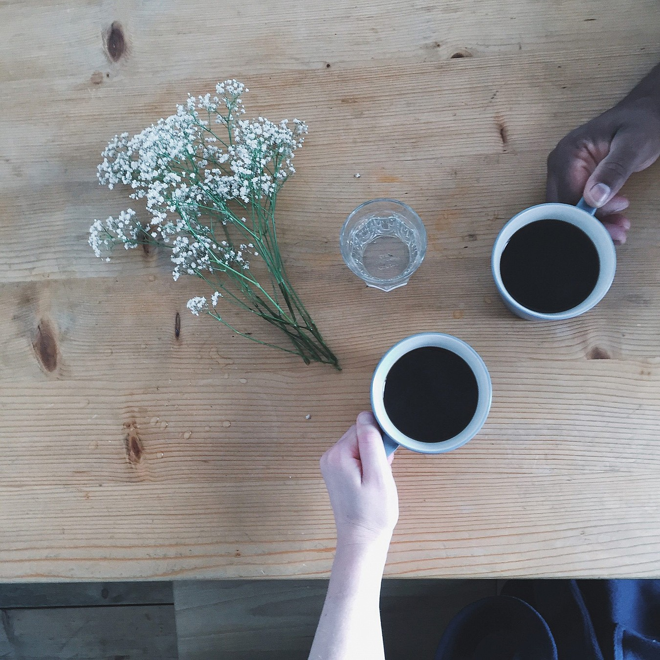 Overhead shot of two people picking cups of black coffee up from a table.